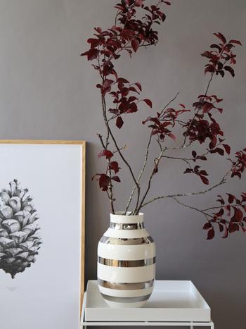 葉の付いた「枝もの」を楽しむなら、シックな色味のものをチョイス。モダンなアートやフラワーベースをコーディネートしたインテリアに、ベニスモモの深い赤茶色が差し色になって、ぐっと空間が引き締まります。どっしりとしたフラワーベースなら安定感があり、大きな「枝もの」を生けるのにもおすすめ。