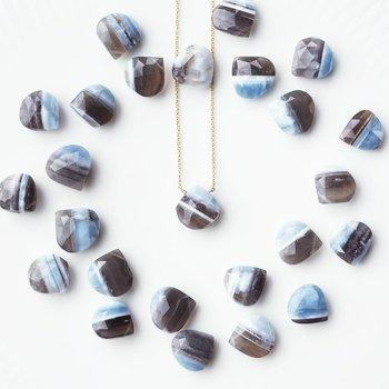 瑪瑙とほかの貴石が、長い時間をかけて一体化した石もあります。こちらのストライプブルーオパールは、瑪瑙とブルーオパールが縞模様に生成したもの。縞瑪瑙のように交錯した部分をカットして宝飾品に使うと、どちらの石の美しさも備えた希少な輝きを楽しめます。