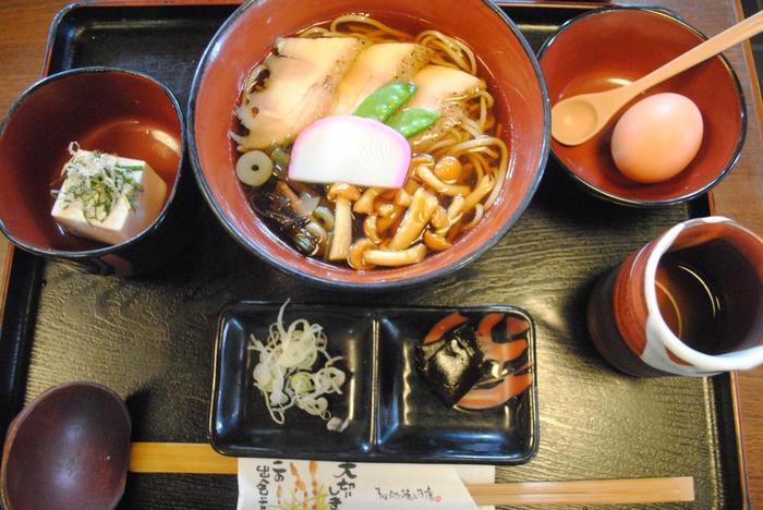 メニューは、『天ぷら蕎麦』や『鴨南蛮蕎麦』等など、蕎麦(うどん)各種が揃う他、唐揚げや天ぷらといった定食、豆腐のサラダや焼き鳥といった一品料理等、種類豊富です。  看板メニューは、『大名そば』。ローストした地鶏がトッピングされた温かい蕎麦に、湧水で作った豆腐や温泉卵がついた人気の蕎麦セットです。