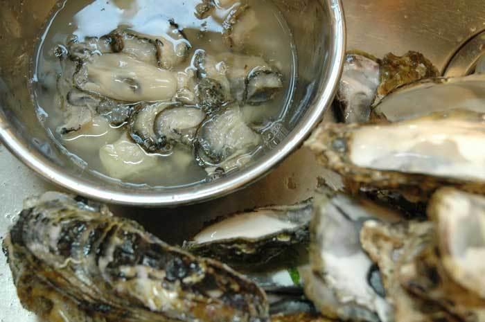 まずは、軍手と先のとがっていないテーブルナイフを用意。牡蠣の平らな面を上にして持ち、ちょうつがいを手前に。先の広がっている部分の合わせ目にナイフを入れ、小刻みに動かしながら貝柱を切ると、上の貝殻がはずれます。同じように下の貝殻にくっついている貝柱を切り、上でご紹介したように洗ってから調理しましょう。