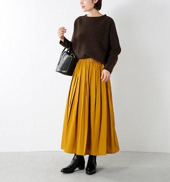 一歩間違えると老けて見えるブラウンのニット。マスタードのフレアスカートを持ってこれば、華やかでフレッシュなコーディネートに仕上がります。