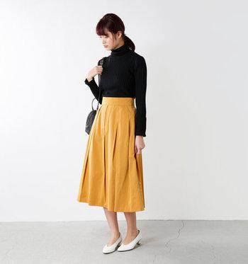 ブラックのタートルニットは便利な一方で、その色と形で重たい印象になりがち。ボトムがマスタードのスカートなら、グッと軽やかで爽やかな着こなしに。