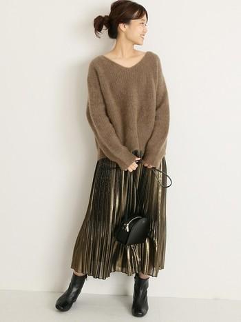 トップスがボリュームのあるセーターで、ボトムのプリーツスカートが透けや光沢を感じる軽い素材。素材使いにメリハリのあるコーデは、秋冬ならでは!