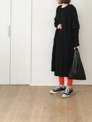 シックなブラックコーデは、足元にサーモンピンクのレギンスを忍ばせて。意外性のあるカラーブロックで技ありモードを堪能。