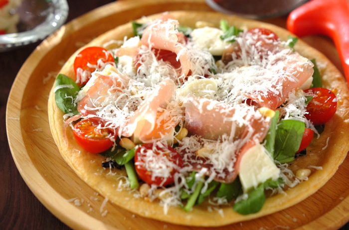 市販のピザクラストを焼き上げてから、サラダの材料をトッピングしていきます。チーズをたっぷり散らすと贅沢な雰囲気のひと品に仕上がります。