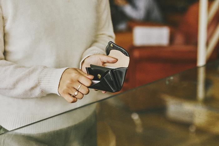 フラップで開閉するタイプの小ぶりなお財布は、ころんとしたシルエットがなんとも可愛らしいアイテム。内部は3つに仕切られ、コイン、カード、お札と分けて整理しやすい仕様になっています。中央のポケットはスナップボタンがついているので、鍵などを収納しても良さそう。