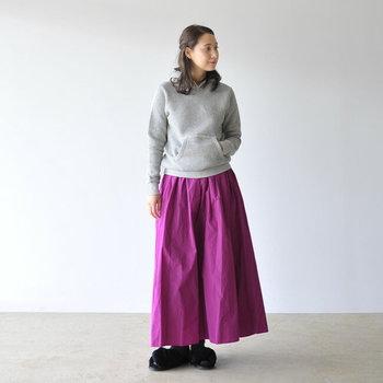 定番のグレーのプルオーバーパーカーは、艶やかなパープルのスカートで女性らしく印象チェンジ。