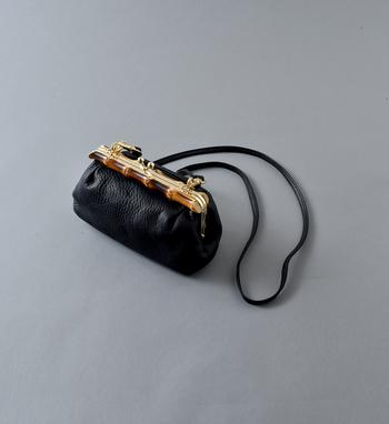 こちらも上と同じくPOMTATAのもの。こちらのバッグはがま口部分にバンブーをあしらった珍しいデザイン。シボ感のあるレザーの素材感と一緒になって深みのある表情を見せてくれます。ちょこんと小ぶりなサイズ感が大人かわいいバッグです。