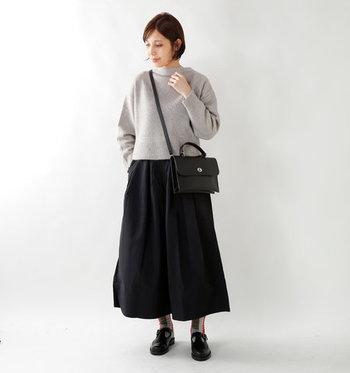 グレーのハイネックニットは、黒のロングスカートと合わせてとことんシンプルに着こなして。首が詰まっているハイネックは全体が重たく見えがちなので、デザイン靴下で遊び心をプラスしているのがポイントです。