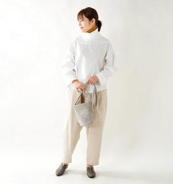 ハイネックの白シャツに、あえてタートルニットをレイヤードしたスタイリングです。パンツもアイボリー調のワントーンで揃えているので、マスタードカラーのインナーが程よい差し色になっています。