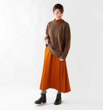 肩や袖にゆとりのあるニットトップスなら、ワンピースの上にレイヤードしたスタイリングもおすすめです。ブラウン×オレンジのカラーリングが、秋冬らしさ抜群で好印象。