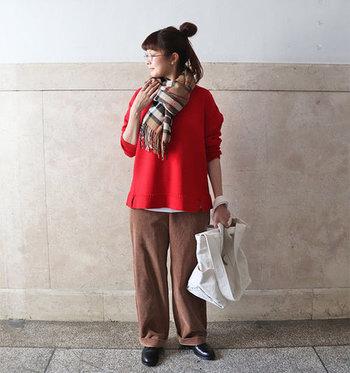 季節感たっぷりな赤色ニットの裾から、さりげなく白インナーを見せたスタイル。ブラウンのワイドパンツと合わせて、見えるか見えないかくらいの覗かせ方が、おしゃれ上級者のイメージを与えてくれます。