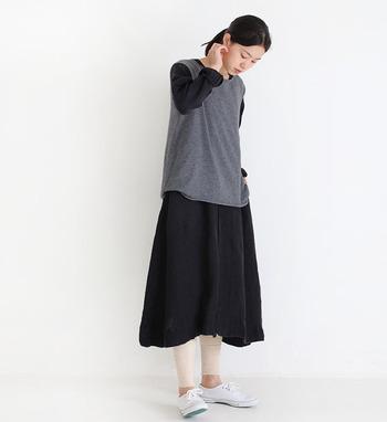 黒のワンピースに、グレーのニットベストをレイヤードしたスタイリング。ベストなら袖がない分、ちょっぴりボリューム感のあるワンピースでも重ねやすいのがポイントです。