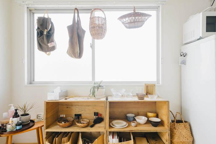 あちこちに置かれた生活用品をひとまずカゴやボックスに入れると、それだけでお部屋から圧迫感がなくなります。上からほこりよけの布をかぶせて、中が見えないようにしちゃいましょう。