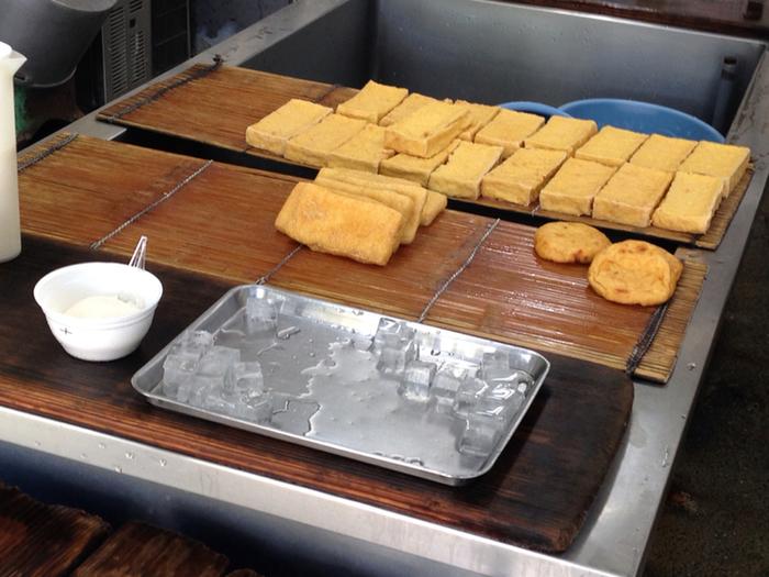 「豊島豆腐店」は、大豆の自然な甘みがしっかり味わえる『汲み豆腐』が名物です。  店では、冷やし固める前の豆腐を掬い上げた『汲み豆腐』をその場で味わうことが出来ます。濃厚な大豆の旨味と甘み。ふわっとしてとろっとした食感がたまらない美味しさです。(お土産用の『汲み豆腐』もあり) 【店の人気商品『生揚げ』と『油揚げ』、手前の白椀が名物の『汲み豆腐』】