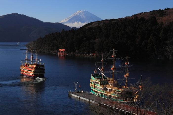 赤い鳥居、富士山、湖面に映る遊覧船は、芦ノ湖を代表する景色です。特にこの景色をしっかり味わえるのが、空気が凛として冴え渡った、晩秋から冬の季節です。  【芦ノ湖の周遊船は、小田急系列の「箱根海賊船」と伊豆箱根鉄道の「箱根芦ノ湖遊覧船」がある。港も航路も、料金体系も異なるので、フリーパスの有無によって選ぶと良い。どちらも年中無休だが、冬期(12月1日~3月19日)は便数が減るので要注意。(画像は、大晦日の海賊船・元箱根港)】