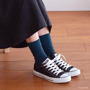 半端丈のブラックのスカートとコンバースのあいだに深みのあるグリーンのソックスをプラス。落ち着いているのに個性を感じる、大人にぴったりの合わせ方です。