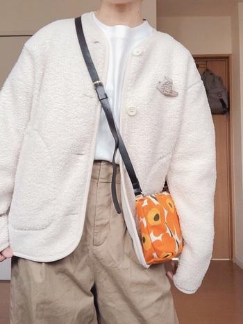 コンパクトなのでバランスが取りやすい、ユニクロのフリースノーカラージャケット。ベージュのワイドパンツと合わせた、冬らしいワントーンコーデ。ビビッドなオレンジのバッグが、着こなしのポイントです。