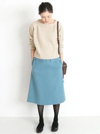 ベージュのニットプルオーバーにサックスブルーのスカートをあわせたスタイリング。足元は黒でまとめていますが、バッグど同色のブラウンのタイツで馴染ませるのも◎