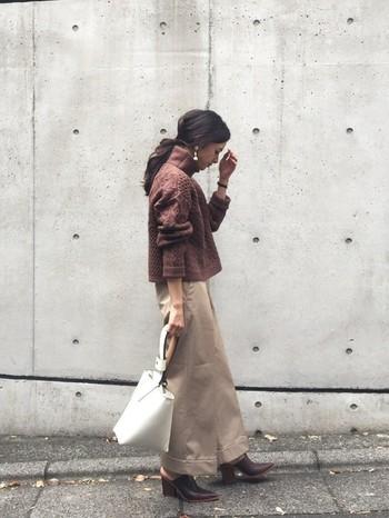 赤みがかったくすみブラウンにベージュのボトムスを合わせ、同系色で大人っぽくまとめたスカートスタイル。シンプルな中にも、ニットのボリューム感とサボのエッジが効いています。