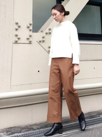 くすみブラウンのカラーパンツに白トップスを合わせたシンプルスタイルは、顔周りが明るく見えますね。トップスとパンツの丈感を短めにして、重めの黒ブーツも軽やかなバランスに。