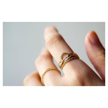 カラーの異なるゴールドは一本一本のリングを華奢にしてリズム感をプラス。インパクトフルながらも統一感ある手元は、リングの幅感とデザインテイストが近いリングをセレクトしているからこそ。