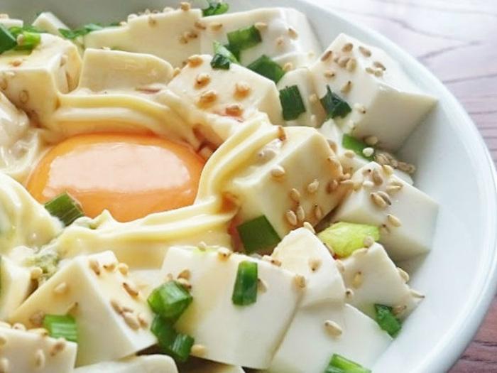 冷やご飯と卵の白身をいっしょに器にもり、レンジで温めます。卵の黄身を白身のうえに戻して、あとは普通の豆腐丼と同じ手順。冷蔵庫でストックしてある冷やご飯をそのまま卵と加熱して一石二鳥です♪