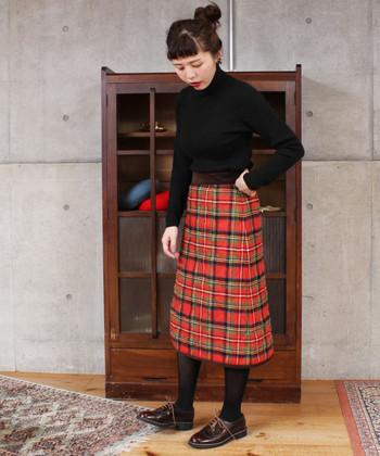 明るいチェック柄のキルティングスカートが引き立つように、他のアイテムは暗めの色で統一。ニットはウエストINしてすっきりと。