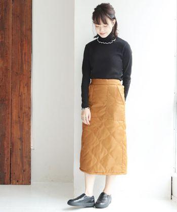 ブラックのニットと、こっくり感のあるキャメルベージュのキルティングスカート。落ち着いた配色で、ワンツーコーディネートを女性らしく上品に導いて。