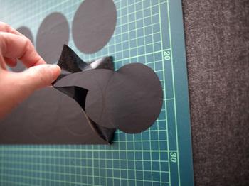 幅広な黒のマスキングテープをコップの底などに当てて丸くカッターナイフでカットしていきます。