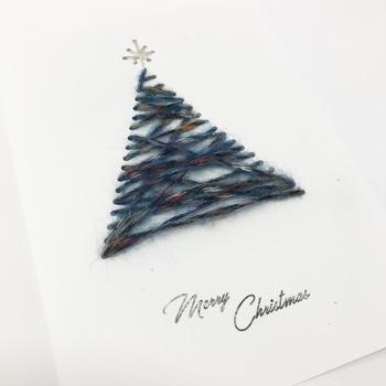 毛糸を紙に通してクリスマスツリーの形にしたカード。シンプルながら、カードが少し立体的になり、おしゃれでスタイリッシュな仕上がりに。