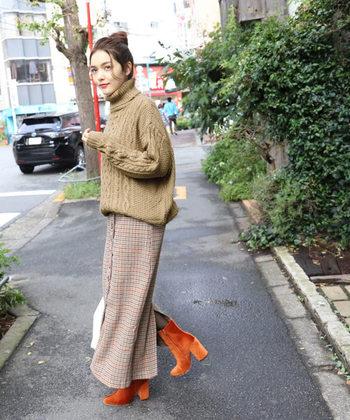 チェック柄のスカートとあわせれば、旬のスタイリングに。 ブーツもオレンジ色で、さりげなくワントーンコーデが完成されていますね。