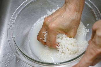 米をとぎます。ボウルに米が浸かるくらいの水を一気に加え、サッとかき混ぜたら、素早く水を捨てます。乾燥した米は、急速に吸水するので、最初の水はぬかが溶け出しやすく、それを吸水させないようにするためです。 再び米が浸かるまで水を入れたら、少し水を捨て、水が少なくなった状態で、手のひらを使い、米全体を軽く握るように20回程度かき回します。
