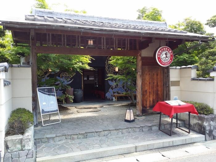昔の日本家屋を改装して作られた「イクスカフェ嵐山」。高級料亭と間違えてしまいそうなほど、情緒があり落ち着いた雰囲気が漂っています。中に入ると小さな日本庭園があり、それを眺めながらお茶することができる贅沢な空間が広がっています。