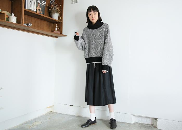 細かいドットを全面に施したタートルネックのニットトップスは、黒のスカートやシューズと合わせたモノトーンコーデに。細かめなドット柄なら、シックな印象で着こなせますね。