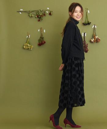 黒のジャガード生地に大きめのドットがあしらわれたスカートは、全身黒でまとめた着こなしに。足元には赤色のパンプスを合わせることで、パーティースタイルにもOKの華やかさをプラスしています。