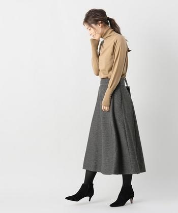 こちらのフレアスカートは、小さなドット柄でさりげないガーリーさがアクセントに。ベージュのタートルトップスをタックインして、オフィスカジュアルとしても活用できる着こなしです。