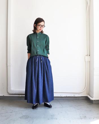 ギャザーの入ったデニムのロングスカートに、グリーンのシャツをタックインしたスタイリングです。深みのあるカラーシャツを選べば、カジュアルなデニムスカートをしっかり格上げできます。