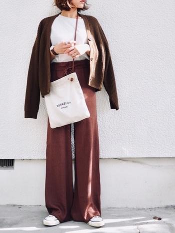 くすみダークレッドのワイドパンツに、ブラウンのカーディガンを羽織った秋冬らしい同色系のスタイリング。柔らかなニット素材がウォーム感を高めています。