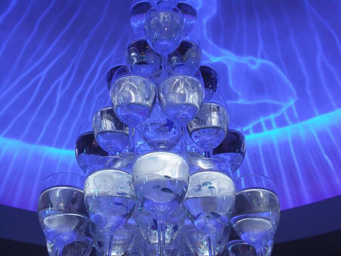 館内にはいろいろなツリーが飾られていますが、その中でも必見なのが、こちらのクラゲのツリーです。59個のワイングラスが6段、ツリーのような形に積み上げられているのですが、なんと、その1つ1つにミズクラゲが入っているんです。  下からのライティング効果もあいまって、ミズクラゲがキラキラとした美しさを放ちます。きっと見とれてしまいますよ。