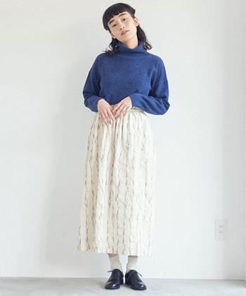 ホワイトのスカートにブルーのニットを合わせ、爽快なフェミニンルックに。スカートに施された繊細な刺繍が、コーディネートの女性らしさを後押し。