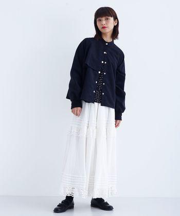ジャケットが持つ辛さをガーリッシュなフレアスカートで中和。中に着たドット柄のトップスはあえて見えるようにして、ネイビーとホワイトの潔い配色に奥行きを。