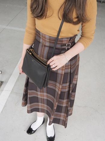 ブラウン×カラシのスカートには、チェック柄にも入っているカラシ色トップスを合わせて。ポシェットとバレエシューズでお上品に。