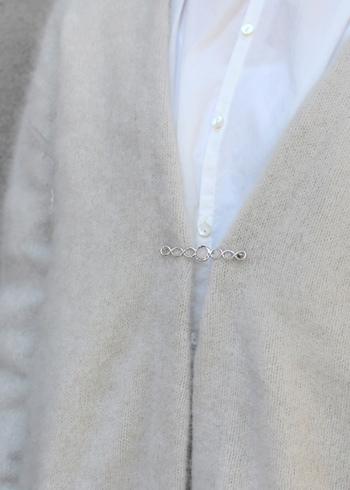流れるように繊細なシルバーのピンに、乳白色の天然石をはめ込んだブローチ。襟元だけでなく、ニットのフロントを留めるにもどうぞ。