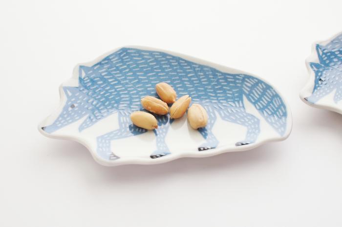 型紙摺りや銅版転写など、印刷による絵付けのことを指す「印判手」という技法で作られた豆皿。かすれやにじみ・ムラなどが現れやすい技法ではありますが、その不揃い感が味わい深い表情を生みます。 オオカミのイラストが描かれた豆皿は、絵本の中から飛び出してきたようなデザインが魅力的。お菓子をのせたり、アクセサリートレイにするのもいいですね。