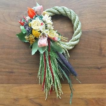 片方に飾りを寄せたとってもキュートなしめ縄飾り。淡い色合いのお花もこんな感じで飾ることでより上品になります。