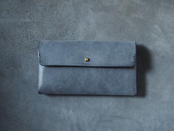 牛革を仕立ててつくられた、グレーブラックの色味が美しい長財布。  長財布としては一回り小さい、17cmというサイズで作られています。持ってみると、手のひらにやさしく馴染みます。
