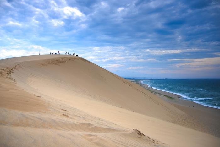 鳥取県鳥取市、日本海岸線に広がる鳥取砂丘は、鳥取のシンボル的存在でもあり、世界中の観光客が訪れる有名スポットでもあります。 国の天然記念物にも指定されている鳥取砂丘は、観光出来る砂丘としては、日本最大規模。白砂が広がる砂丘と、その向こうに見える穏やかに広がる日本海の美しさはとにかく絶景で、訪れた人々は、その圧倒的な存在感と世界観に魅了されます。