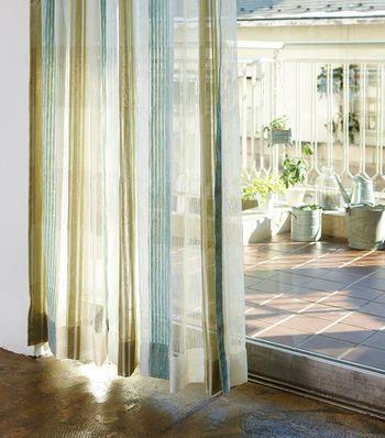 透け感のあるマルチストライプ柄のカーテンは、光の当たり方によって様々な色の表情が楽しめます。ナチュラルな木製の家具や観葉植物にもマッチして、ヘルシーなイメージを演出。