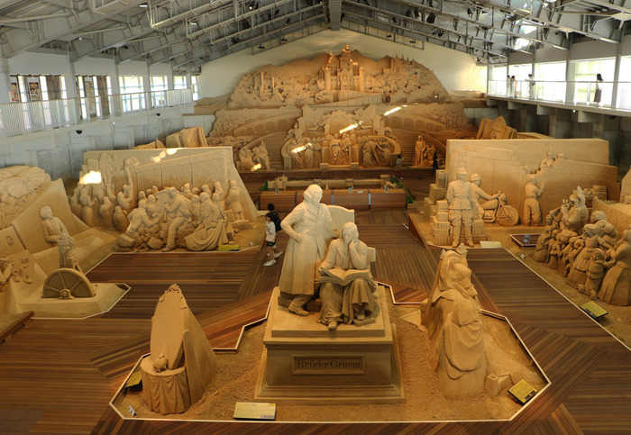 砂丘のすぐ傍にある「砂の美術館」は、世界トップレベルの砂像を、毎年違ったテーマで展示する、世界初の砂像専用屋内施設です。 3階建ての建物の1階は、パネル展示室、2階が砂像展示室、3階が展示の全景を見ることのできる回廊とミュージアムショップとなっています。館内をゆっくりと鑑賞した後は、屋外の展望広場に足を運んでみてはいかがでしょう!雄大な鳥取砂丘を一望することが出来ます。 で砂丘を訪れた際は、是非、砂の造形美が生み出す素晴らしい作品を、その目で実際に体験してみませんか!
